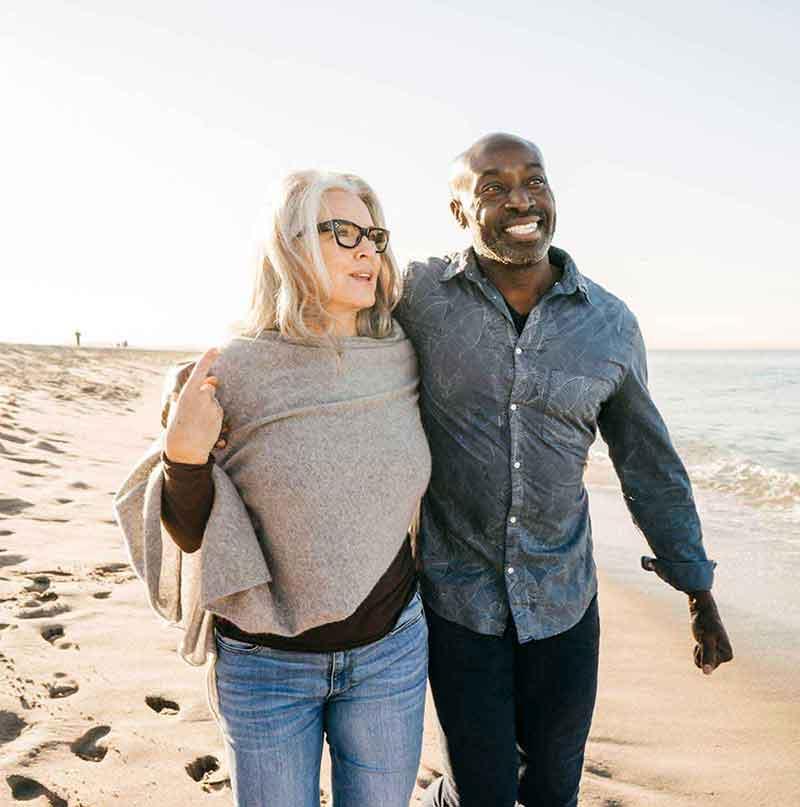 Mixed race couple walking on beach and enjoying life despite having hearing loss.