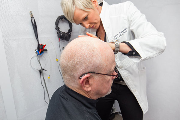 Patient having his ears checked during a hearing loss screening.