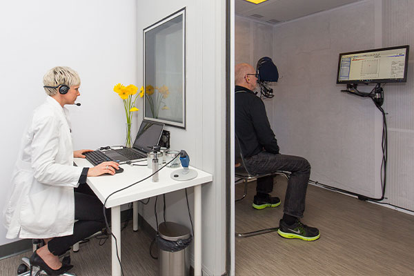 Patient in a hearing booth getting a  hearing screening test at Blue Sky Hearing.