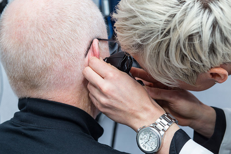 Audiologist looking in a man's ear.
